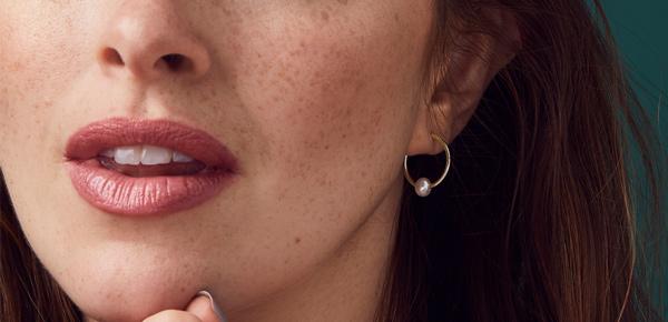 Model wearing pearl hoop earrings