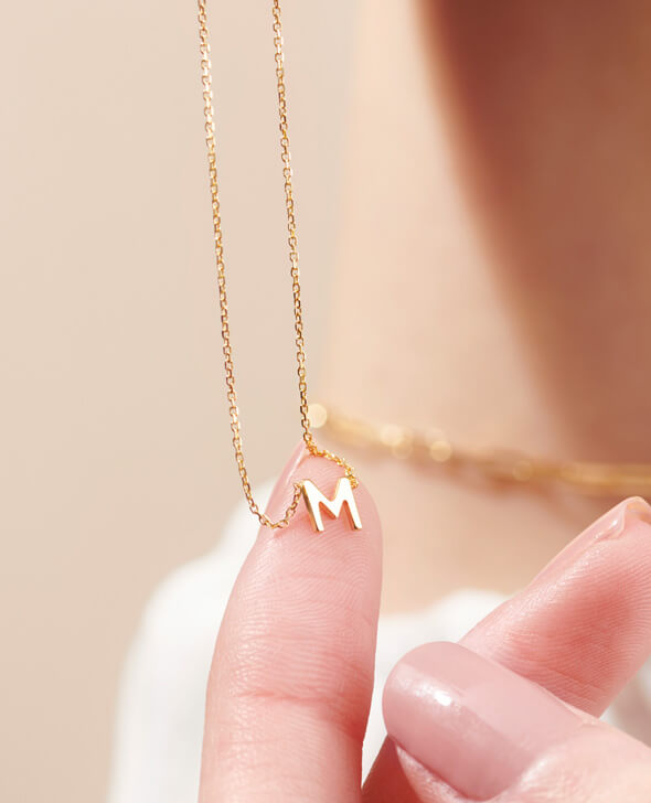 Model holding a gold letter M necklace.