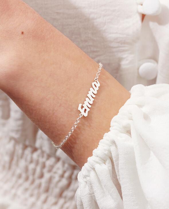 Model wearing carrier style name bracelet in silver