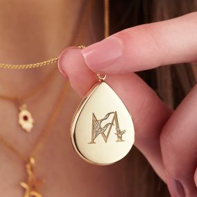 hand holding an engraved initial gold locket