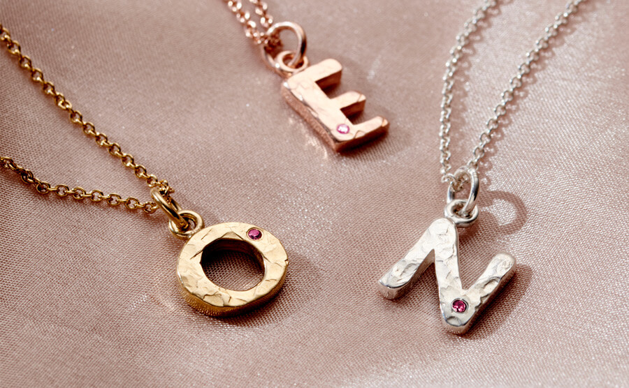 textured letters set with ruby birthstones
