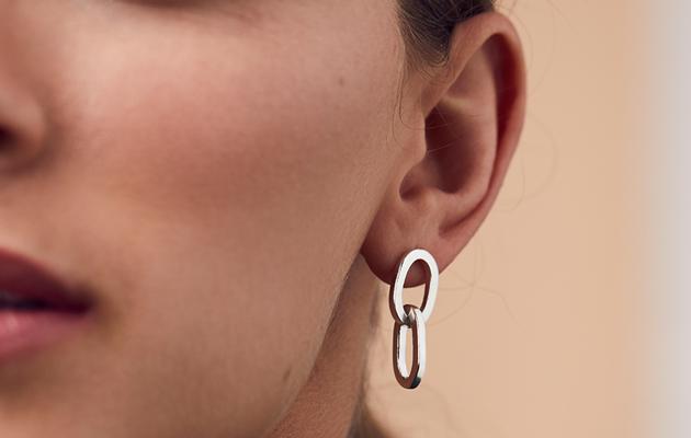 model wearing large link stud earrings