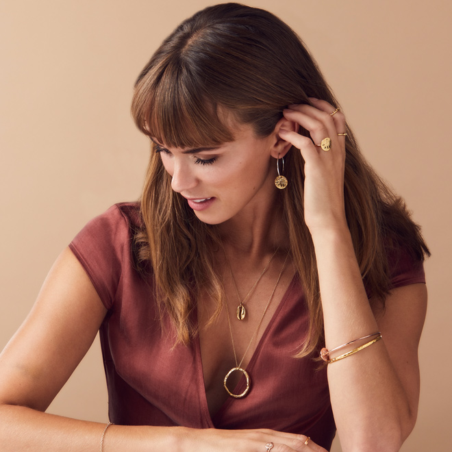 model wearing gold disc necklace