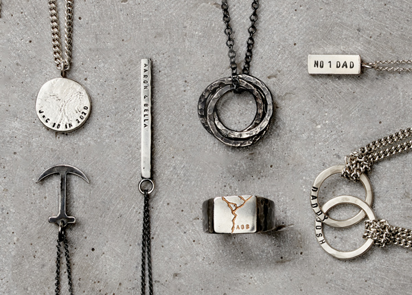 Collection of personalised silver men's jewellery laid on concrete.