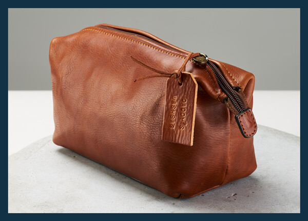 tan leather wash bag with a personalised leather tag