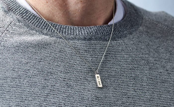 Male model wearing a silver necklace with a personalised tag