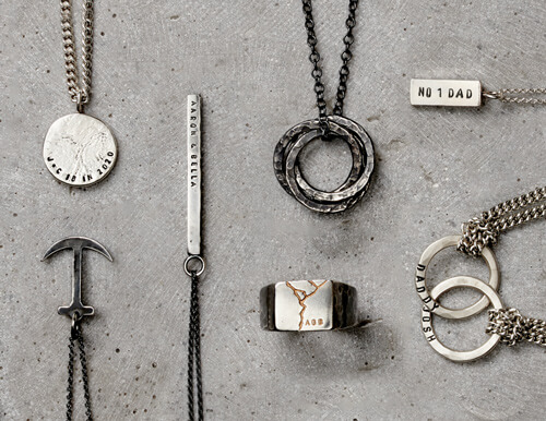 men's jewellery laid out on a concrete background