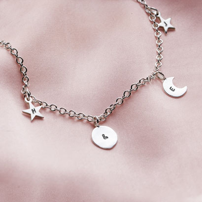 silver bracelet with personalised star and moon charms