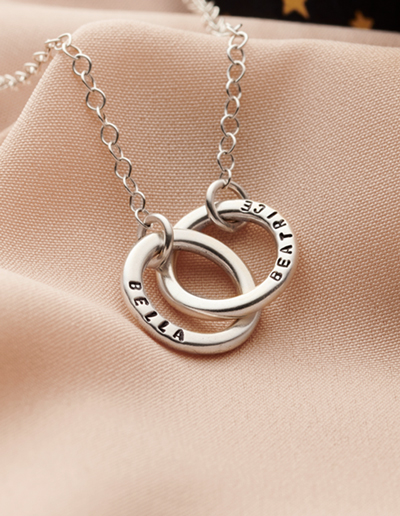 personalised silver hoop necklace on pink background
