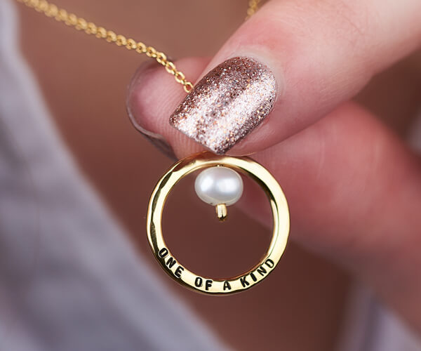 gold pearl necklace personalised with the words one of a kind