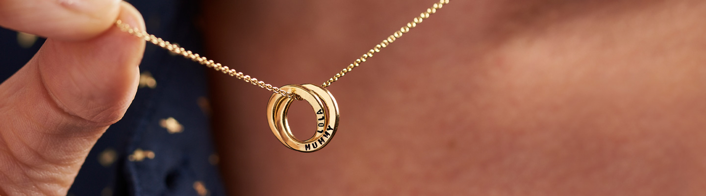 Gold plated two ring russian ring necklace held by a model